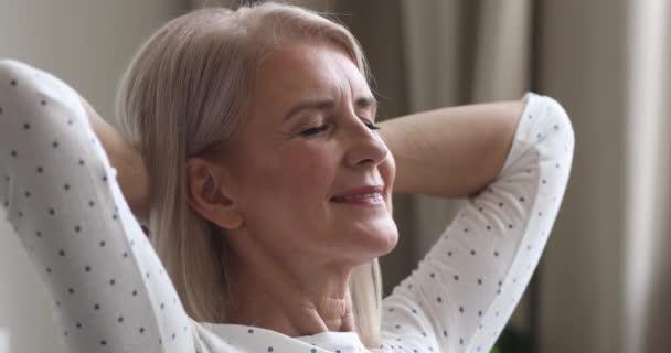 glücklich verträumte ältere Frau entspannen die Hände hinter dem Kopf zu Hause
