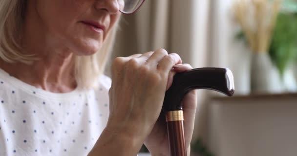 Rozrušená starší žena držící hůlku, smutná, zblízka