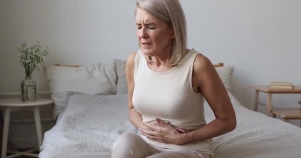 Nemocná starší žena držet břicho pocit bolesti břicha v posteli
