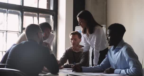 Vážná manažerka a různorodý tým analyzovat papírování na setkání