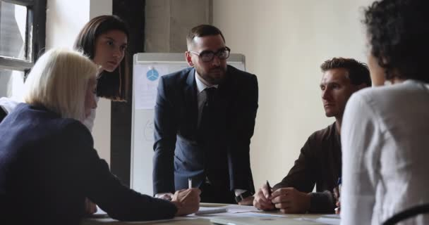 Sokszínű munkacsoport ötletbörze a papírmunka az irodai eligazító asztalnál