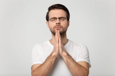 Concentrated young prayer in eyeglasses with closed eyes folding hands and hoping for all best, asking for health, good luck, help. Head shot praying man isolated on grey studio background portrait. stock vector