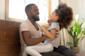 Photo African father tickles little daughter family having fun indoors