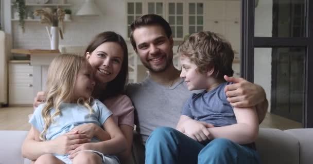 Happy caucasian parents holding on laps smiling children.