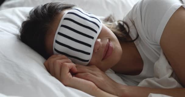 Klidná mladá dívka v noční masce, odpočívající v pohodlné posteli.
