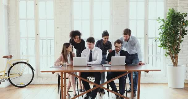 Multiethnic business team brainstorm using computers in modern office