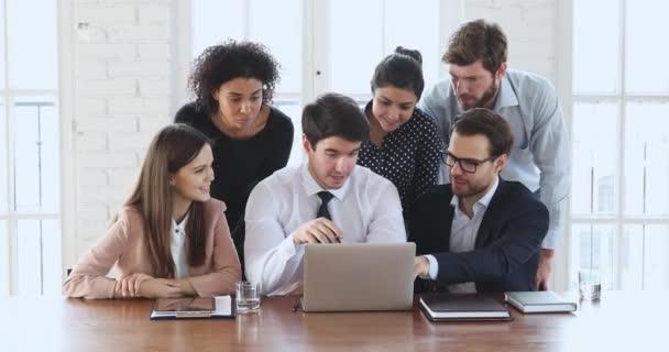 Různé etnické skupiny zaměstnanců diskutovat digitální data na notebooku