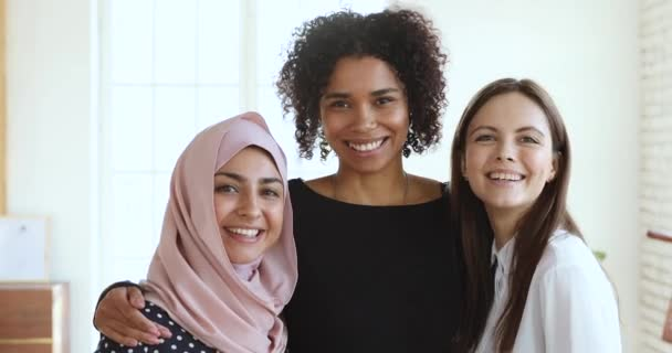 Three multicultural smiling young women friends embracing looking at camera