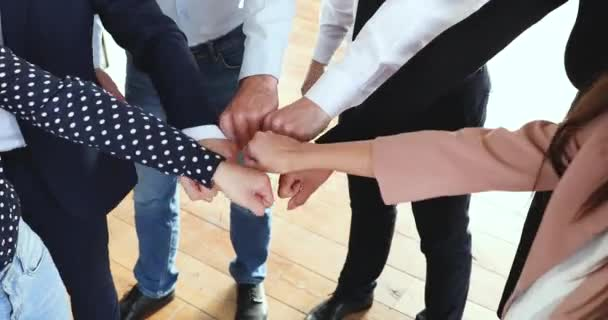 Reliable business team people join fists together in circle, closeup