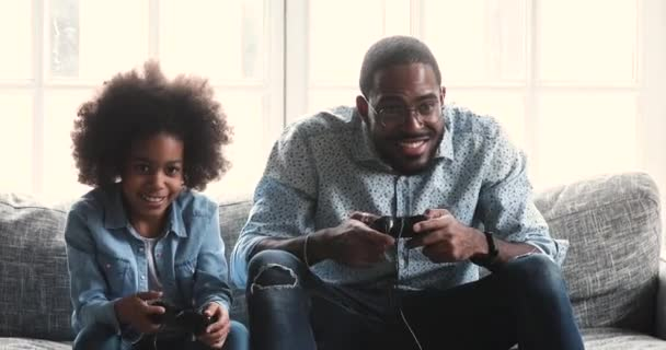 Happy african dad and child daughter playing winning video game