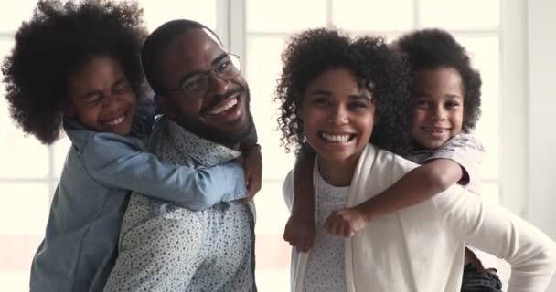 Happy african parents piggyback children look at camera, family portrait