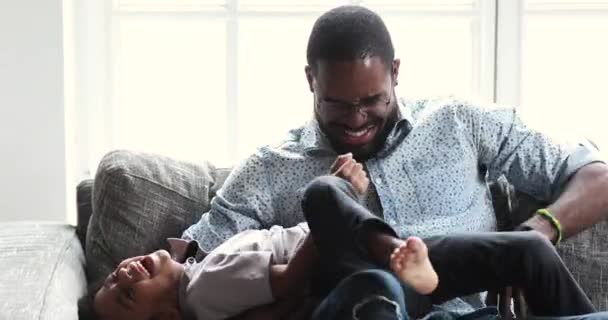 Funny happy african daddy tickling cute small son on sofa