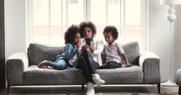 Šťastný africký maminka sledování smartphone videa baví s dětmi