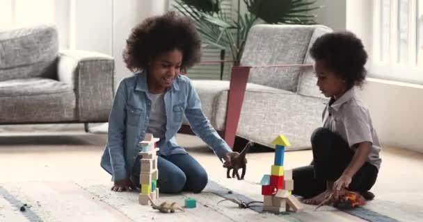 Šťastné africké děti hrající hračky sedět na podlaze doma