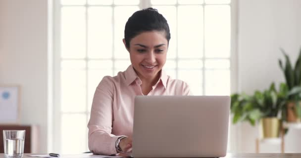 Excited indian businesswoman winner celebrating online win looking at laptop