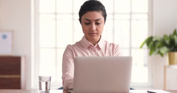 Young indian businesswoman relaxing at office desk finished computer work
