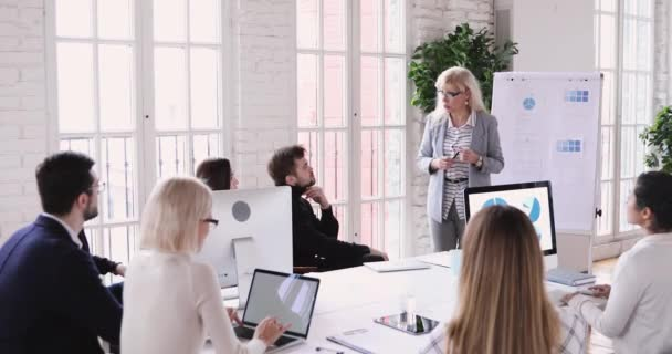 Professional mature businesswoman manager give flip chart presentation at training