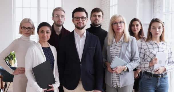 Confident smiling successful multicultural professional team looking at camera