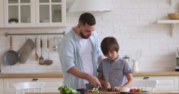 Mladý otec učí malý školní chlapec syn sekání čerstvé zeleniny.