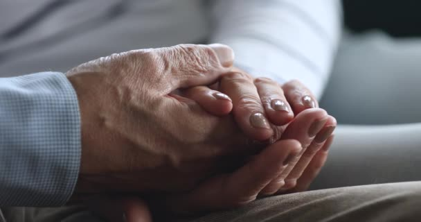 Nahaufnahme einer älteren Frau mit faltiger Hand ihres Ehemannes.