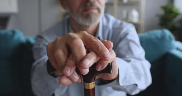 Close up older disabled sad man holding hands on cane.