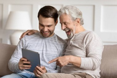 Smiling young man showing funny photo on tablet to father.