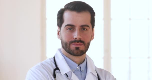 Smiling confident male doctor wear white uniform looking at camera