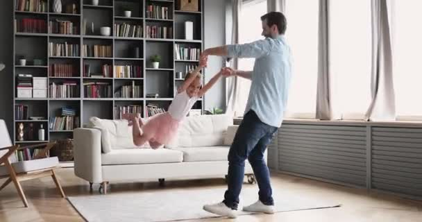 Loving father having fun spinning with child daughter at home