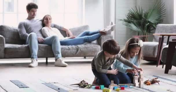 Kids playing while relaxed parents lounge in living room interior