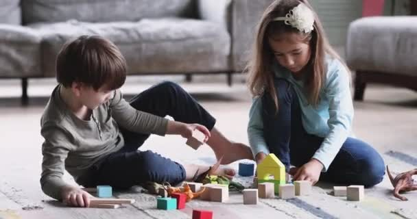 Two kids brother and sister playing wooden blocks on floor