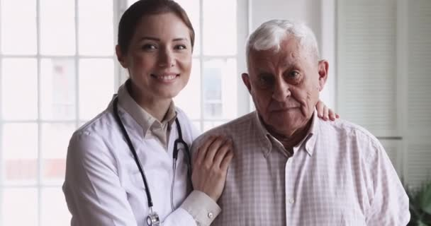 Smiling female doctor embrace happy senior patient look at camera