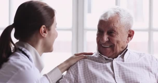 Smiling healthy senior grandpa talk to caring young female doctor