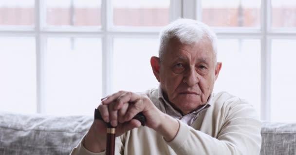 Happy older man hold walking stick looking at camera