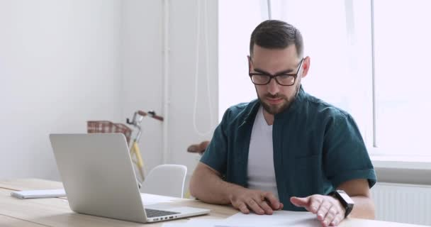 Motivated young male freelancer working on computer, doing paperwork.