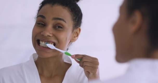 Šťastný zdravý biracial dívka dělá ranní rutinní zubní péče.