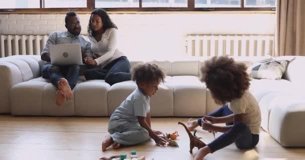 Afrikanisches Paar benutzt Laptop, während Kinder auf dem Boden spielen.