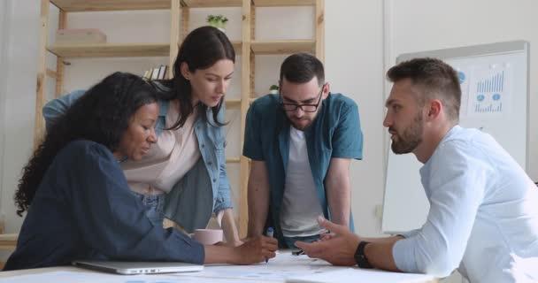 Motivierte Gruppe unterschiedlicher Geschäftsleute diskutiert Projekt.