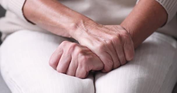 Senior depresivní žena sedí sama s vrásčitýma rukama složenýma
