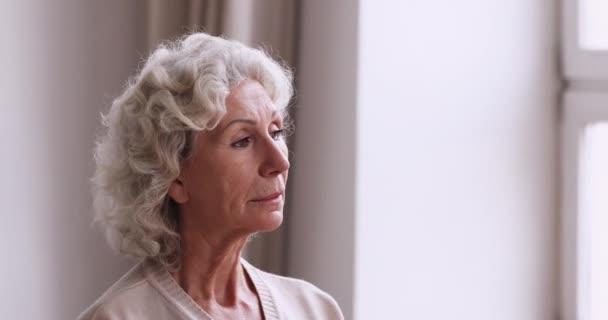 Szomorú idős nagymama egyedül áll az ablakon át bámulva.