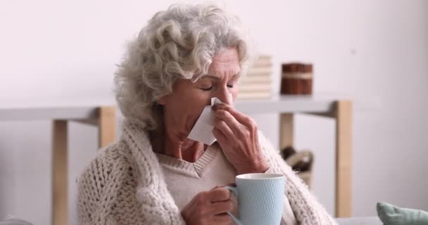 Nemocná starší žena přikrytá přikrývka foukání nos v tkáni