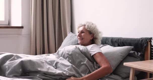 Boldog, friss, idős hölgy egyedül ébred egy kényelmes ágyban.