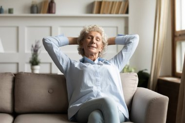 Calm senior woman relax on couch in living room