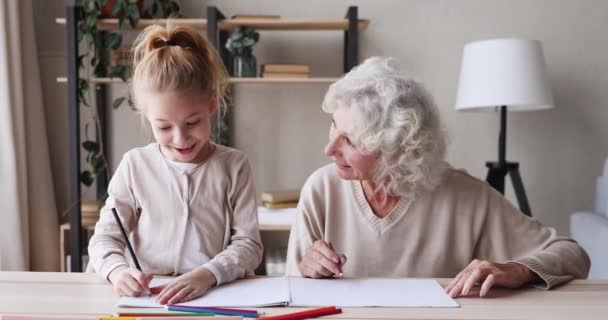 Happy grandmother helping school child granddaughter drawing together