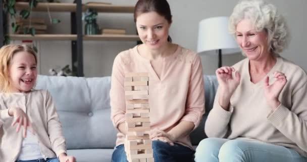 Happy three generations women having fun playing jenga game together