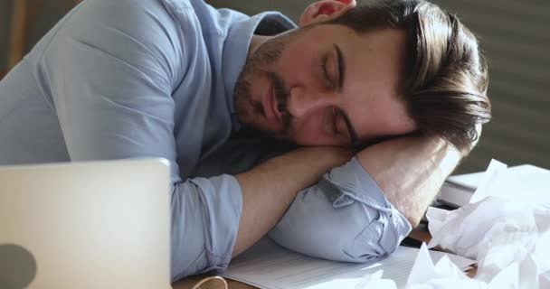 Tired young man office worker sleeping at work desk
