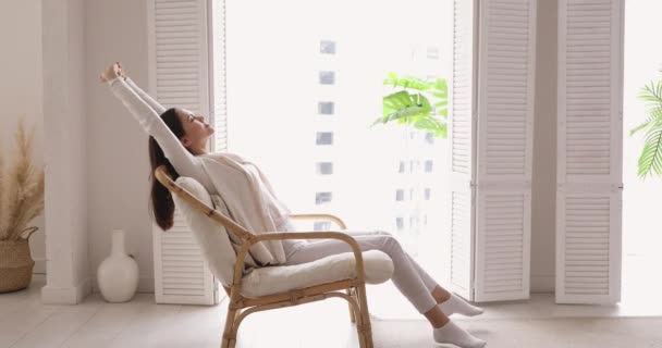 Happy single young woman stretching sitting in comfortable armchair