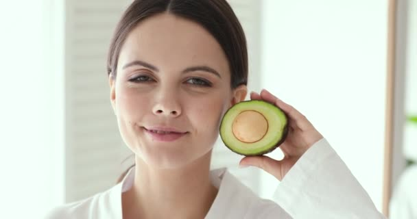 Beautiful smiling girl holding avocado looking at camera, close up