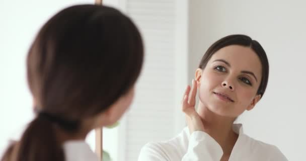 Confident beautiful young woman putting facial cream looking in mirror