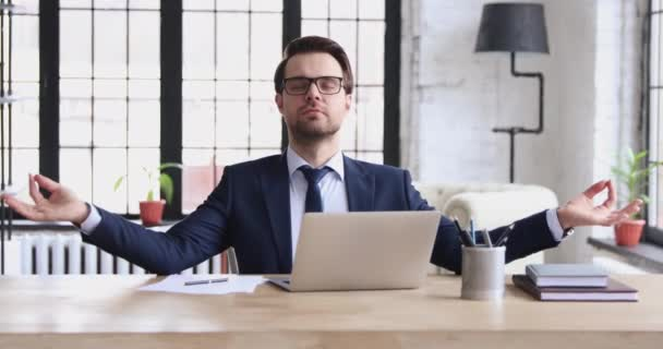 Funny calm businessman meditating sitting at office desk