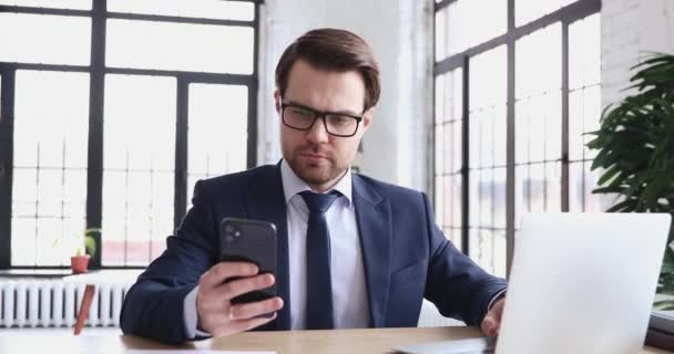 Serious businessman using laptop and modern smartphone in office